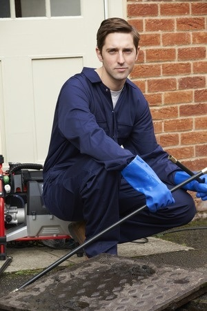 plumber wearing blue rubber gloves and blue uniform crouching on porch with length of pipe