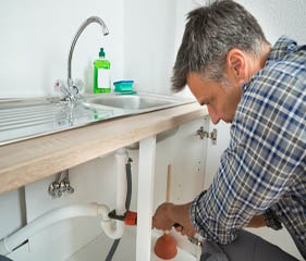 man holding pipe wrench fixing pipe under sink